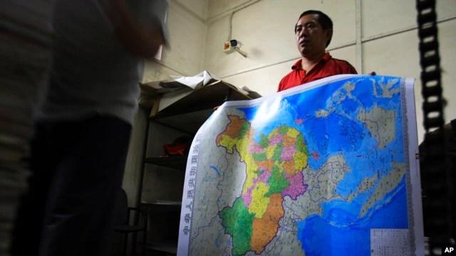 Một nhân viên nhà máy in trong tỉnh Hồ Nam cầm tấm bản đồ Bắc Kinh cho phát hành bao bao gồm các quần đảo và vùng biển mà Trung Quốc tuyên bố chủ quyền ở Biển Đông. (Ảnh tư liệu chụp năm 2014).