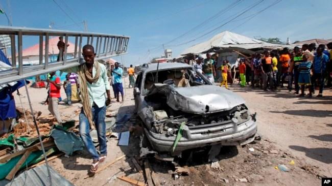 Un hombre pasa por un vehículo destrozado después de una explosión en un mercado en la capital, Mogadiscio, Somalia, el 19 de febrero de 2017.