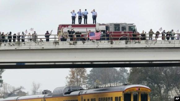 En un paso elevado, los bomberos saludan, junto con otros asistes, al tren que lleva el cuerpo del ex presidente George H.W. Bush.