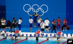 Athletes gather in the pool during a swimming practice session at the Tokyo Aquatics Center for the 2020 Summer Olympics, in Tokyo, Japan, Wednesday, July 21, 2021. (AP Photo/Martin Meissner)