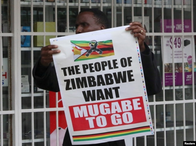 FILE - A man carries a poster calling for Zimbabwe President Robert Mugabe to step down as Zimbabweans take to the streets in Harare, Zimbabwe, Nov. 18, 2017.