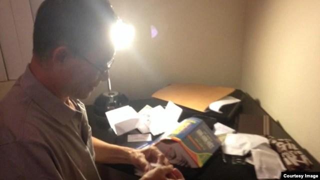Blogger Điếu Cày đang giở những bức thư của bạn tù được ông khâu vào áo và mang qua Mỹ.