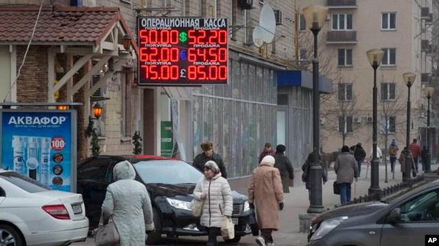 Người dân đi qua một biển tỷ gia hối đoái ở trung tâm Moscow, 1/12/2014.