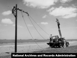 The Rural Electrification Administration (REA) erects telephone lines in rural areas. (date unknown)