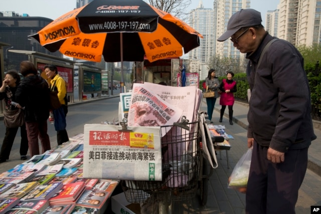 "A man looks at a newsstand with a copy of the day's Global Times displayed on a basket in Beijing, April 5, 2016. The nationalistic tabloid published an editorial saying an unidentified ""powerful force"" was behind the documents leaked from a Panama-based law firm that name relatives of current and retired Chinese politicians, including President Xi Jinping, as owning offshore companies."