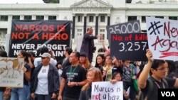 """11月24日,菲律宾首都马尼拉,大学生和民众在拉沙大学门前举行""""噪音抗议""""活动,反对前总统马科斯入葬国家英雄墓园。图为纳瓦罗牧师在发表演讲。(2016年11月24日, 美国之音朱诺拍摄)"""