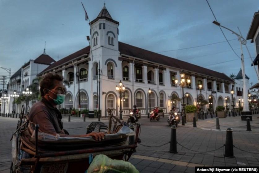 Seorang tukang becak bermasker duduk menunggu pelanggan di lokasi wisata Kota Tua, Semarang, Jawa Tengah, 1 Juli 2021. (Foto: Antara/Aji Styawan via REUTERS)