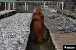 FILE - A Rohingya refugee woman walks through Nazirartek fish drying yard where she works, in Cox's Bazar, Bangladesh, March 23, 2018.