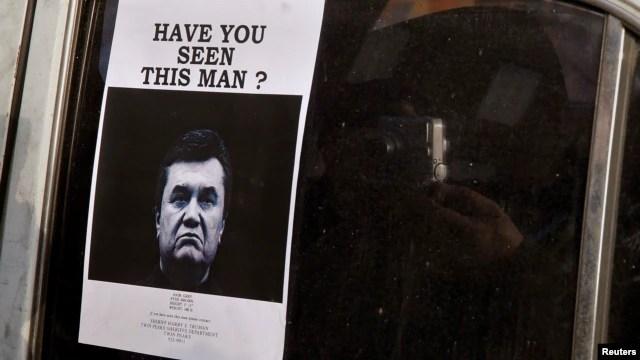 """Ảnh của tổng thống đang đào tẩu Victor Yanukovych với thông cáo """"Truy nã"""" dán trên cửa sổ một chiếc xe hơi dùng làm rào chắn gần Quảng trưởng Độc lập trong thủ đô Kyiv, 24/2/14"""