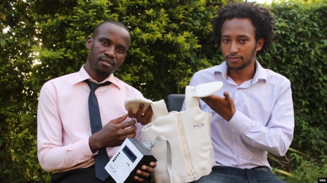 Alumni Makerere University Telecom, Brian Turyabagye (left) and Besufekad Shifferaw (right) show the smart jacket to be used to diagnose pneumonia in children Kampala Uganda 5 April 2017 (photo: H. Althumani / VOA)