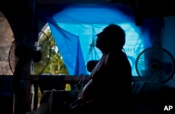 FILE - A man takes one of his 10 a day asthma treatments to help him breathe, inside his home still covered with a tarp a year after Hurricane Maria, in Naranjito, Puerto Rico, Sept. 9, 2018.