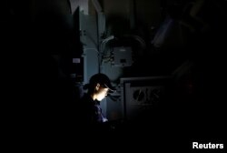 Female IT specialist Airi Azumai checks communication cables on Japanese helicopter carrier Kaga in the Indian Ocean, Indonesia, Sept. 24, 2018.