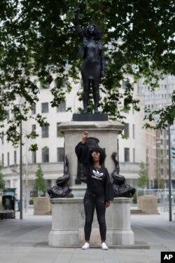 "Jen Reid berpose di depan resin hitam dan patung baja baru yang menggambarkan dirinya, yang diberi judul ""A Surge of Power (Jen Reid) 2020"" karya seniman Marc Quinn, di Bristol, Inggris, 15 Juli 2020."