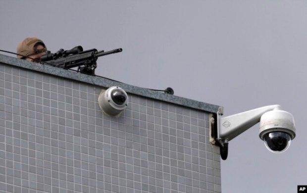 Un francotirador de la policía federal apunta con su arma mientras manifestantes protestan contra el ex presidente de Brasil, Luiz Inácio Lula da Silva, frente al Departamento de Policía Federal en Curitiba, Brasil, el viernes 6 de abril de 2018.