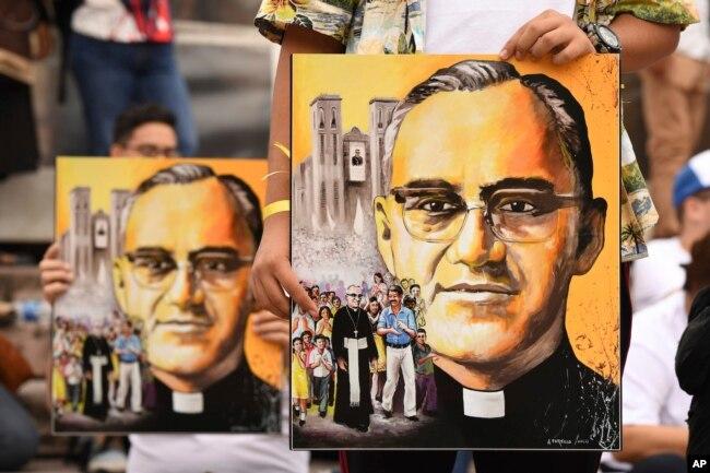 Salvadoreños en procesión sostienen afiches del arzobispo Óscar Arnulfo Romero en San Salvador, el sábado 13 de octubre de 2018. Romero fue elevado a la santidad por el papa Francisco el domingo 14 de octubre de 2018, junto con el papa Paulo VI y otros cinco beatos.