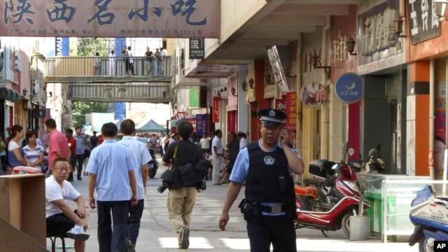 2011年8月2日,一名警察在中国新疆喀什发生袭击的现场附巡逻 (美联社资料照片)
