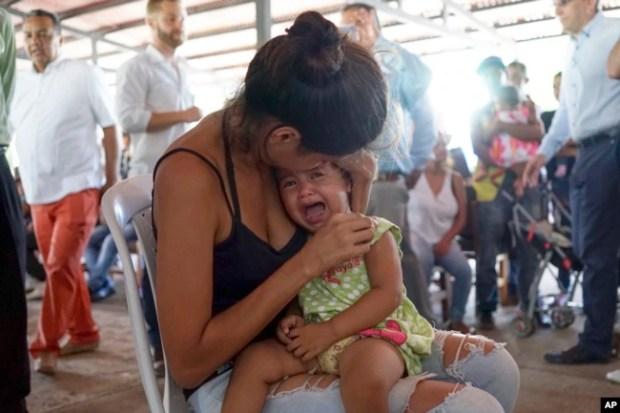 Una mujer venezolana sostiene a una niña en un puesto de salud para migrantes en Cúcuta, a lo largo de la frontera de Colombia con Venezuela, el lunes 16 de julio de 2018.