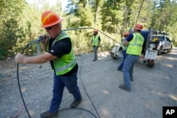 Workers install broadband internet service to homes in a rural area around Lake Christine near Belfair, Washington State, August 4, 2021.