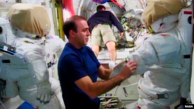 Expedition 38 crew member Rick Mastracchio (L) checks out the spacesuit that he will wear during a spacewalk with crew member Mike Hopkins, in the Quest airlock in the International Space Station in this undated image taken from video from NASA TV, Dec. 20, 2013.