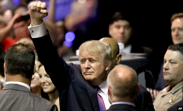 FILE - Republican presidential candidate Donald Trump raises his arm as he leaves after a rally in The Woodlands, Texas, June 17, 2016.
