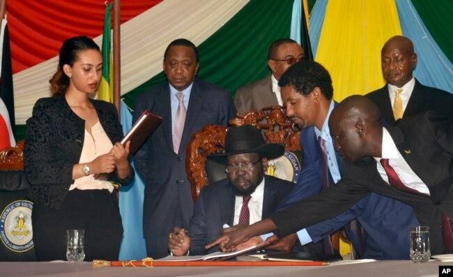 South Sudan President Salva Kiir, seated, signs a peace deal as Kenya's President Uhuru Kenyatta, center-left, Ethiopia's Prime Minister Hailemariam Desalegn, center-right, and Uganda's President Yoweri Museveni, right, look on in Juba, South Sudan, Aug. 26, 2015.