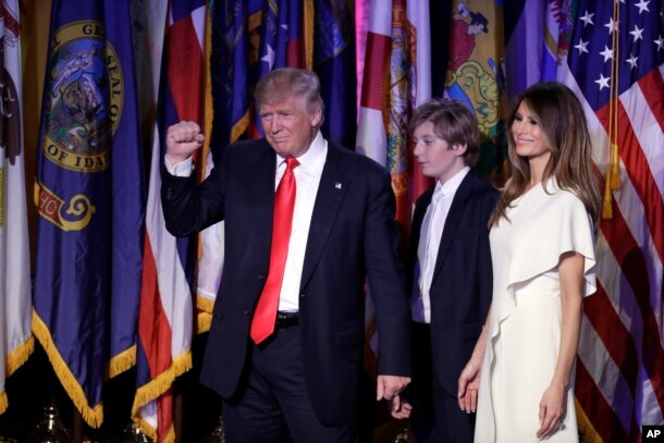 President-elect Donald Trump pumps his fist after giving his acceptance speech as his wife Melania Trump, right, and their son Barron Trump follow him during his election night rally, Nov. 9, 2016, in New York.