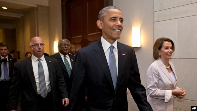El presidente Barack Obama junto a la líder de la minoría en la Cámara de Representantes, Nancy Pelosi, durante su visita al Capitolio este viernes, 12 de junio de 2015.