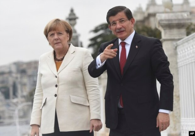 Turkish Prime Minister Ahmet Davutoglu, right, talks to Germany's Chancellor Angela Merkel, left, during their meeting on the grounds of his office in Dolmabahce Palace in Istanbul, Oct. 18, 2015.