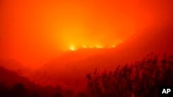 Flames from the KNP complex burn along the side of a hill above the Kaweah River in Sequoia National Park, Calif., September 14, 2021.