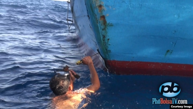 A Vietnamese fisherman repairs his vessel after it was rammed by a Chinese patrol ship that it protecting the waters around a disputed oil rig in the South China Sea, May 18, 2014. (PhoBolsaTV.com)