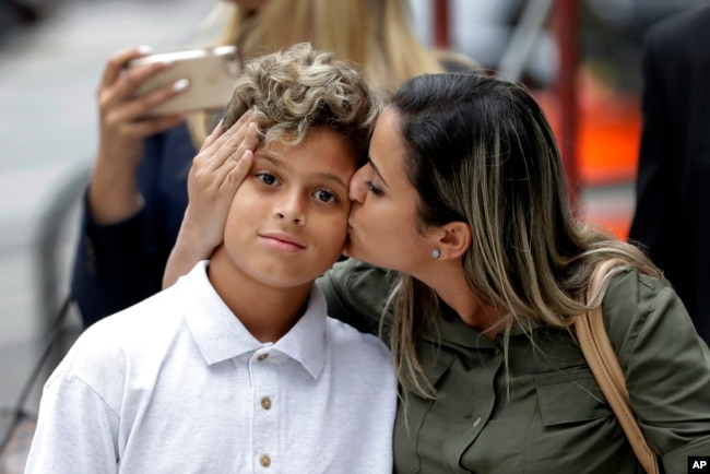 Sirley Silveira Paixao, an immigrant from Brazil seeking asylum, kisses her 10-year-old son Diego Magalhaes after he was released from immigration detention in Chicago, July 5, 2018.