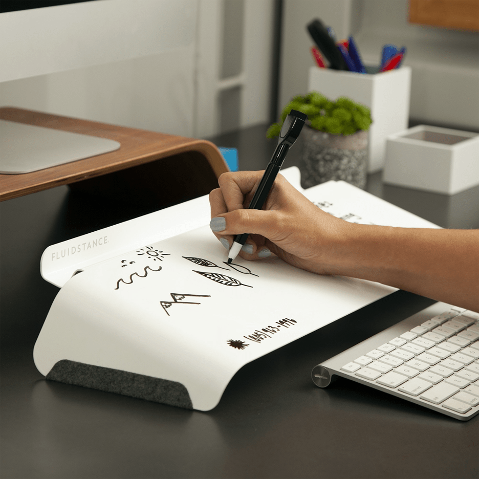 woman writing notes on FluidStance Slope whiteboard on desk office products
