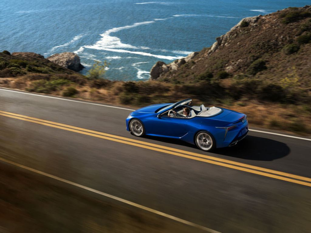 The Lexus LC 500 Convertible driving on a highway along the ocean.