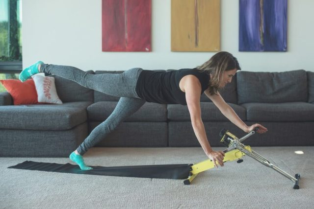A woman using the Ecxy 240 Peloton System in her living room.