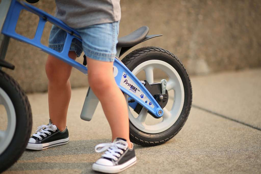 A child using their FirstBIKE on the sidewalk.