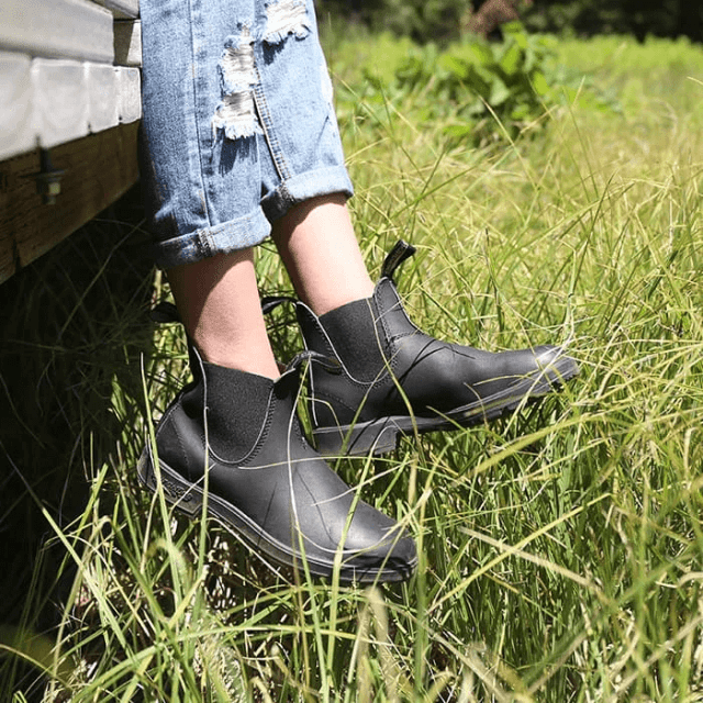 Someone wearing the Blundstone boots while sitting over a field of long grass.