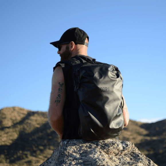 A man sitting on a large boulder carrying the Island Hopper bag from COR surf.