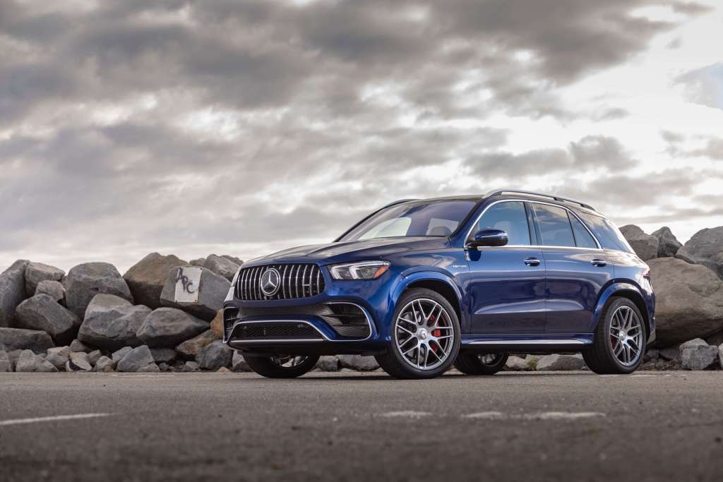 The blue AMG GLE 63 S Coupe on a road next to a pile of boulders.