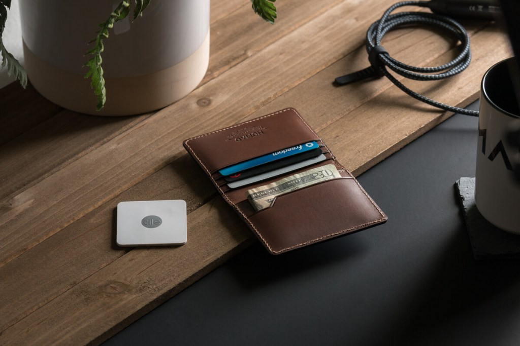 The Slim Wallet with Tile Tracking by Nomad laying fashionably on a desk.