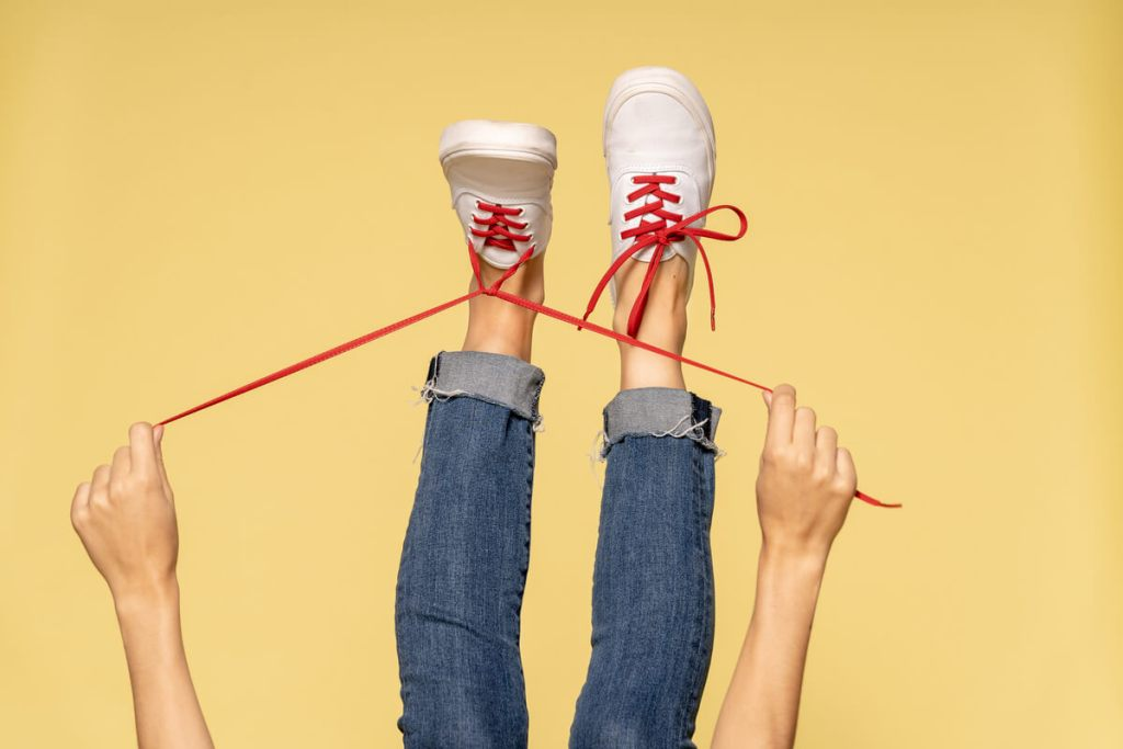 Someone's legs sticking up in the air as they tighten their bright red, Stretchlace shoelaces.