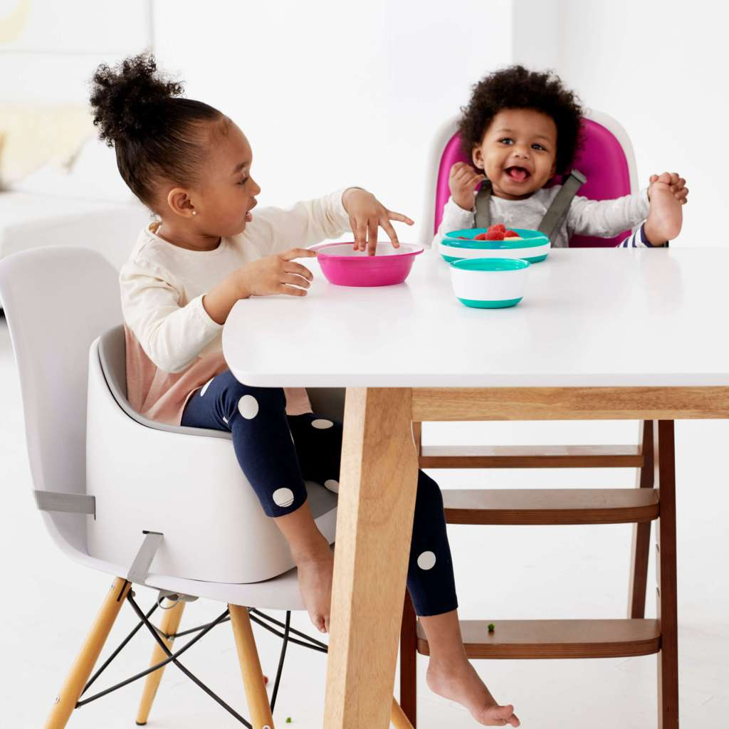 A little girl using her Nest Booster Seat with the removable cushion from OXO as she eats her meal.