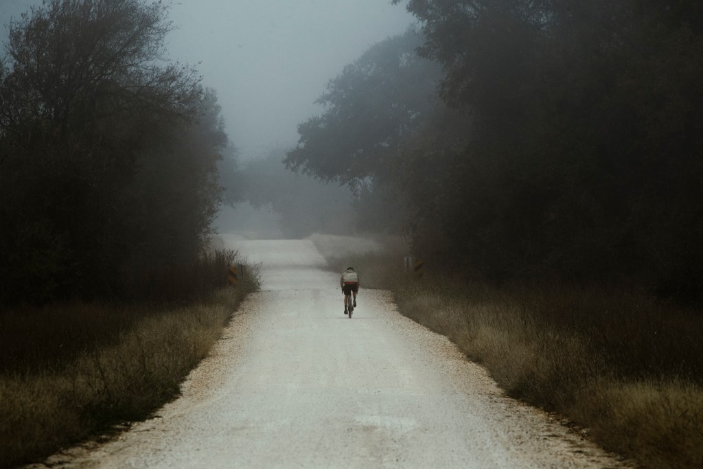 A man riding his Pivot E-Vault down a long dirt road on a beautiful, foggy day.