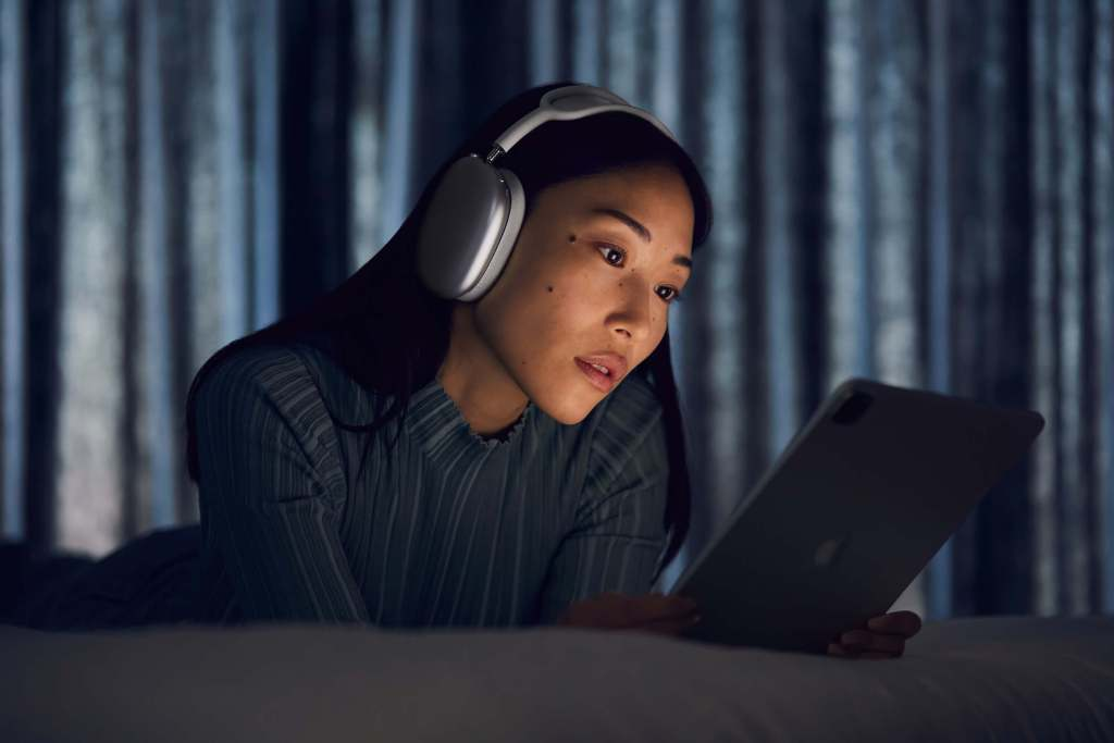 A woman using her iPad while utilizing the Apple AirPods Max.