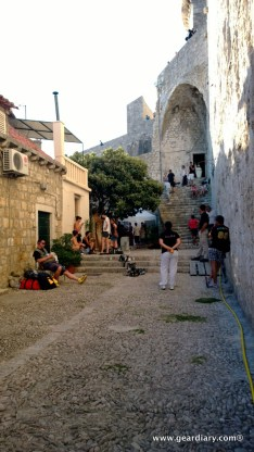 Extras and set workers waiting as a scene is filmed around the corner. Sophie Turner (Sansa) is standing under the trees.