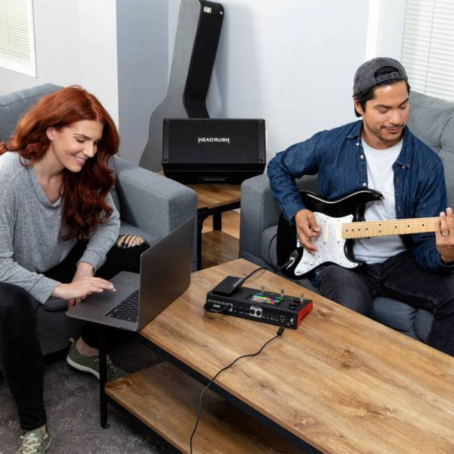 A man plays his electric guitar which is plugged into the HeadRush MX5 while a woman checks the output on her laptop