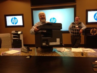 Larry Tracy holding the HP x576dw MFP by the handles