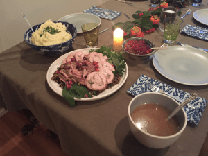 Two place settings, the centerpiece, a candle, the cranberry sauce, mashed potatoes, gravy, and the meat plate.