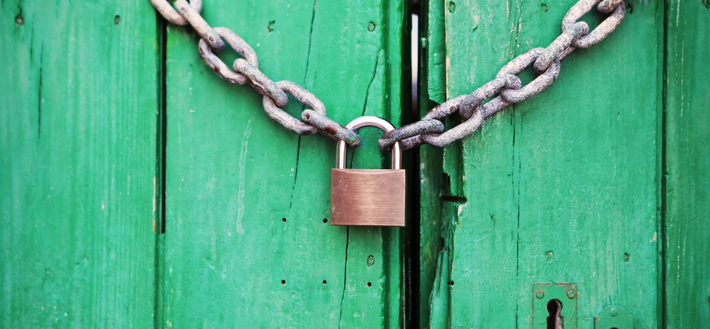 Bronze lock locking a chain across an old wooden door, painted green.