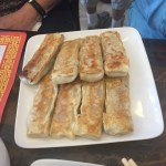 Eight Hui Tou pork dumplings served on a square white plate.