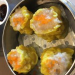 Four pork and shrimp siu mai (dumplings) served on paper in a metal steamer basket.